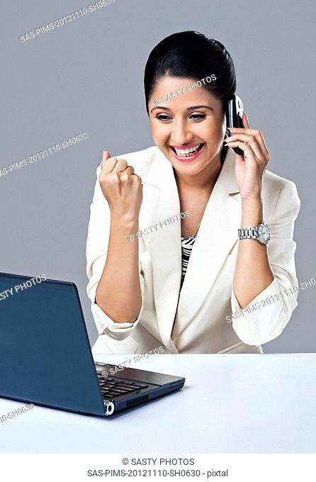 Businesswoman looking excited while talking on a mobile phone in an office