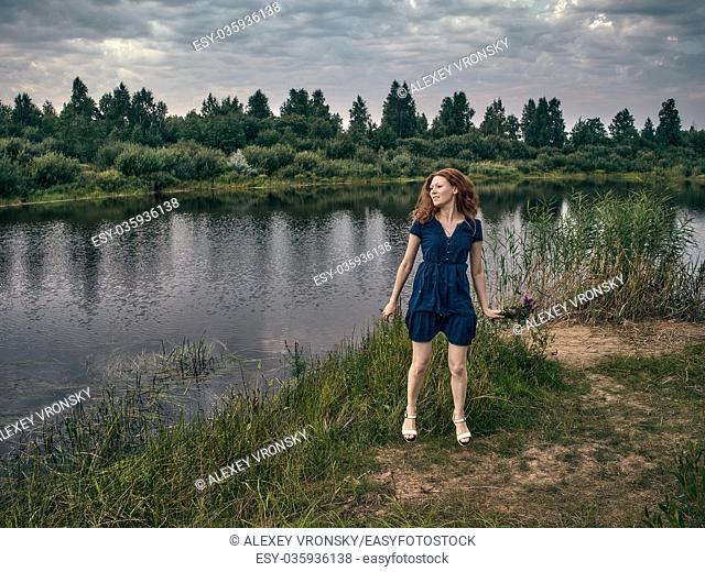 A girl with red long hair strolls along the sandy road along the forest lake. The girl's hair develops in the wind. The girl is dressed summer dress above the...