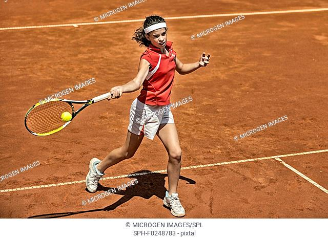Young female tennis player approaching net during game, attacking with forehand