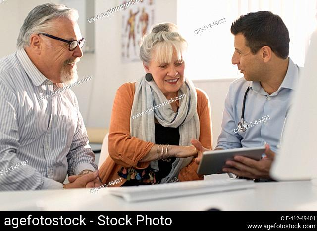 Doctor with digital tablet meeting with couple in doctors office