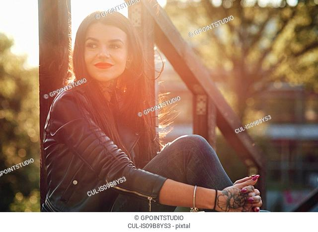 Young woman relaxing outdoors, tattoos on hands