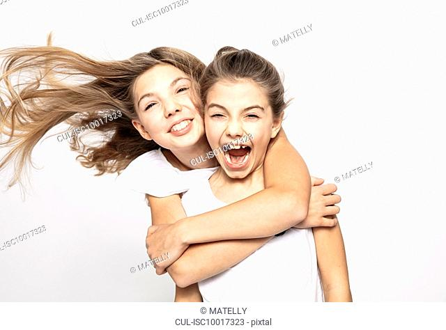 Girl hugging sister from behind, white background