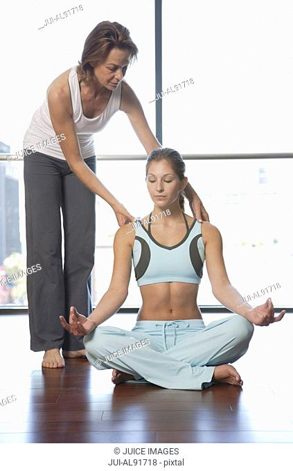 Woman meditating with instructor