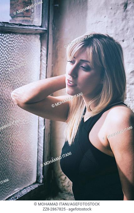 Beautiful young blond woman leaning on the glass looking out of the window