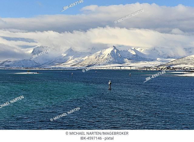Snow-covered mountains with clouds, Risøyhamn with bridge, Andfjord, Andøya Island, Vesterålen, Nordland, Norway