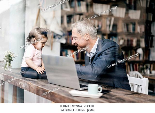 Businessman with little daughter working on laptop in cafe
