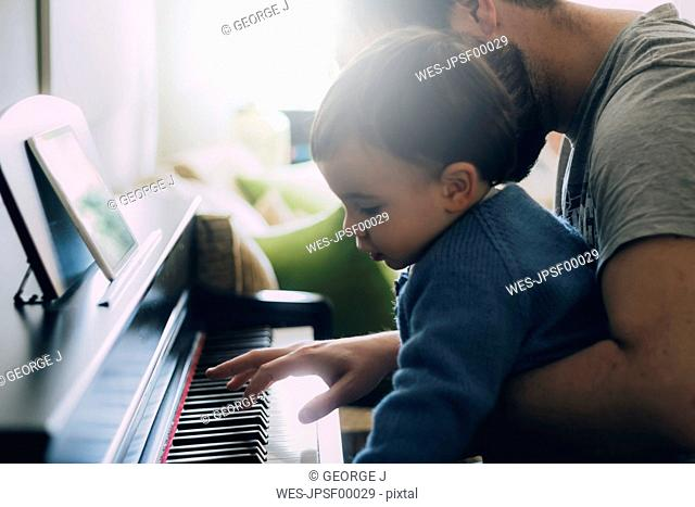 Child and his father playing piano