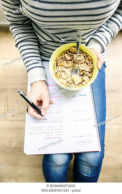 Woman sitting on floor with muesli bowl writing on notepad