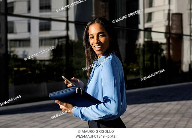 Businesswoman using smartphone, laptop bag
