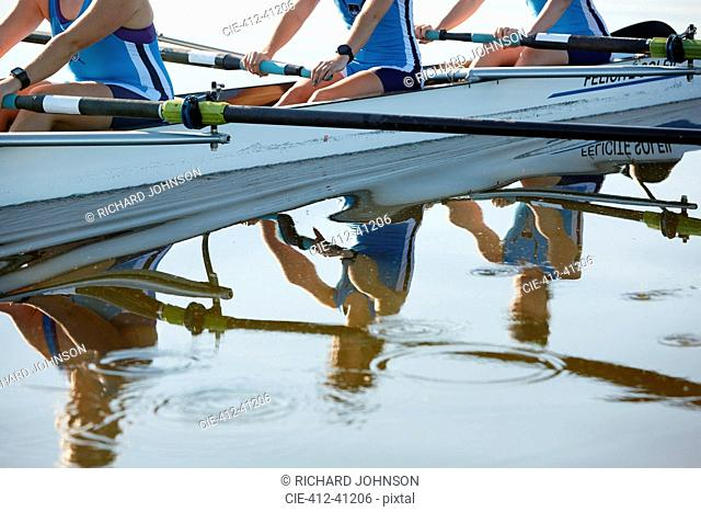 Reflection of female rowers rowing scull on lake