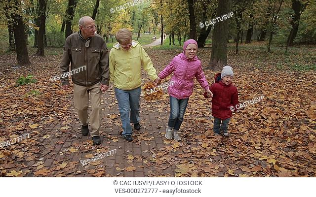 Elderly couple and grandchildren together in autumn