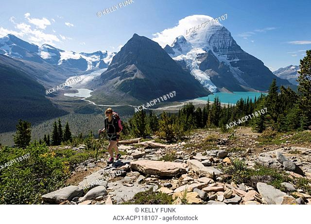 A young woman hikes the Mumm Basis trail with Mt. Robson and Rearguard mountain in the background, Mt. Robson Provincial Park, British Columbia