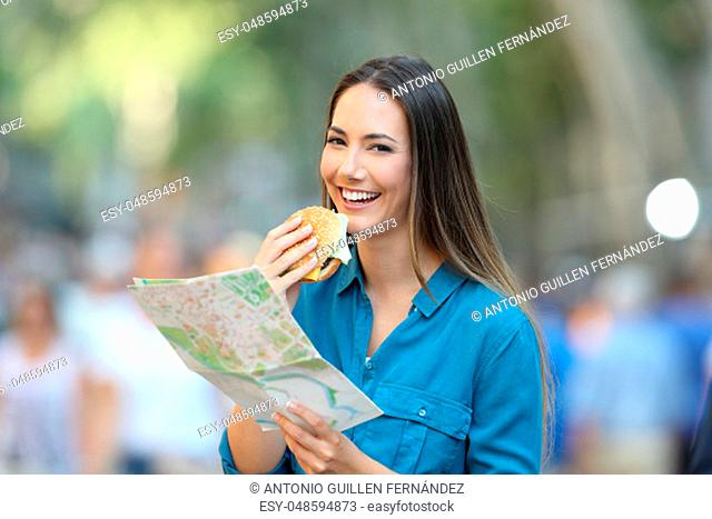 Happy tourist holding a paper map and a burger in the street
