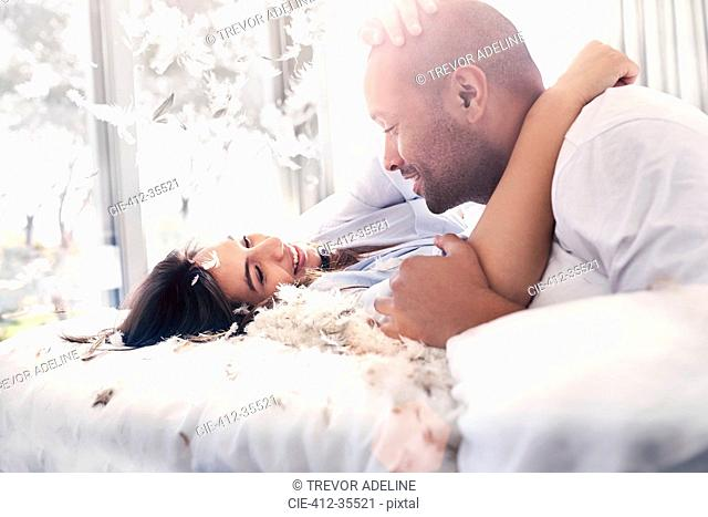 Pillow feathers falling around playful, affectionate couple on bed