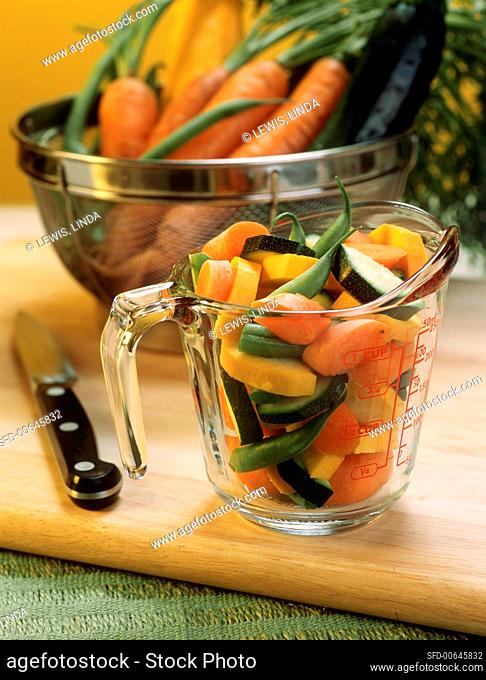 Chopped vegetables in measuring jug on chopping board