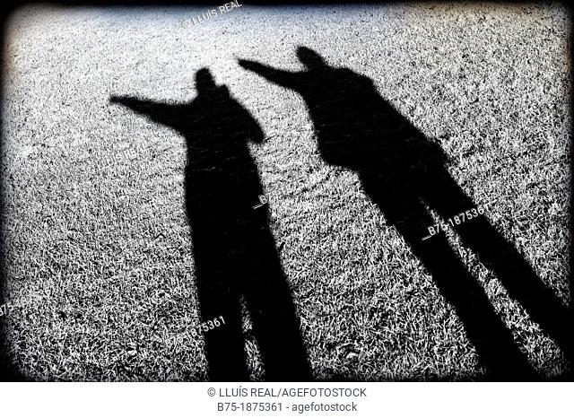 shadow of two people pointing to his left