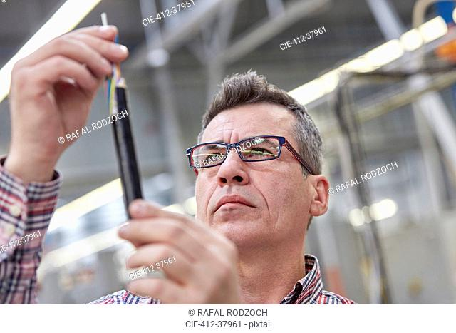 Focused male supervisor examining fiber optic cable in factory