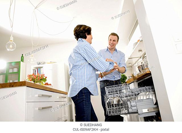 Adult grandson helping grandmother to empty dishwasher