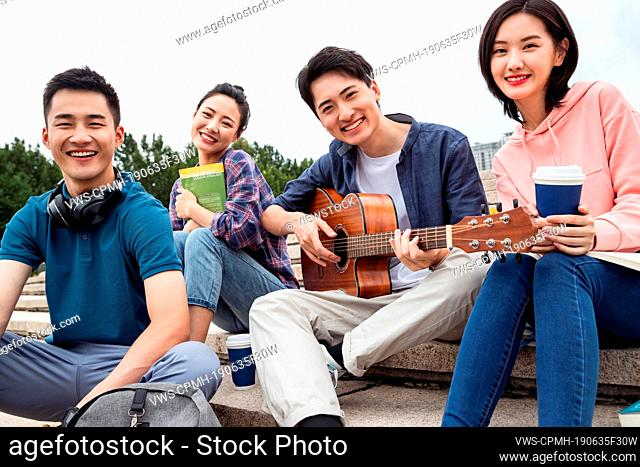 The young college students sat on the steps to play guitar