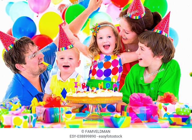 Happy family celebrating kids birthday. Parents and three children celebrate together. Child party with baloon decoration, cake with candles and present boxes