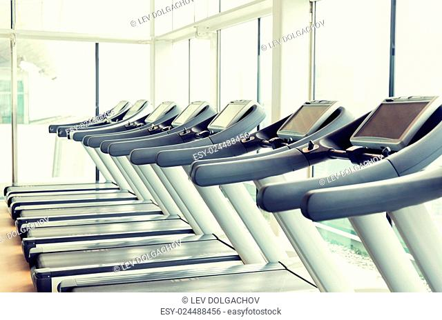 sport, fitness and health care concept - treadmills in gym