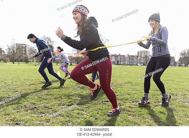 Women exercising, doing team building exercise in park