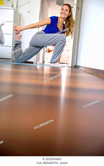 Young woman stretching and exercising at home
