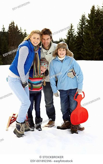 Young Family In Alpine Snow Scene With Sleds