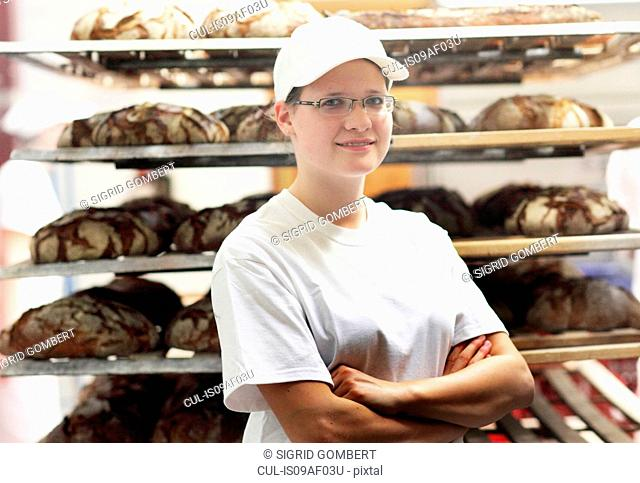 Baker standing in front of bread on shelves with arms folded