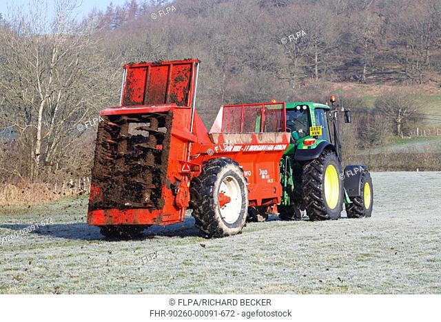 Contractor with John Deere 6520 tractor and K-two Duo muckspeader spreading farmyard manure, in frost covered pasture on organic farm, Powys, Wales, march