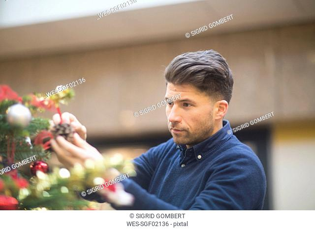 Portrait of man looking at Christmas decoration in a shopping mall
