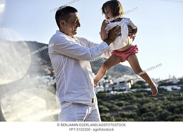 father holding daughter, outdoors in nature. In Chersonissos, Crete, Greece