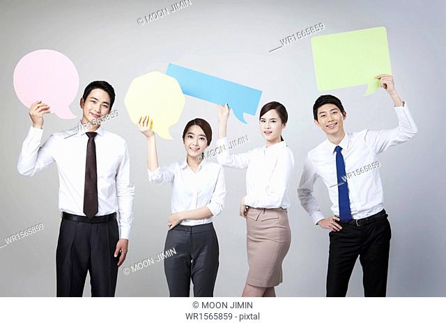 businessmen and women holding different colorful copy spaces
