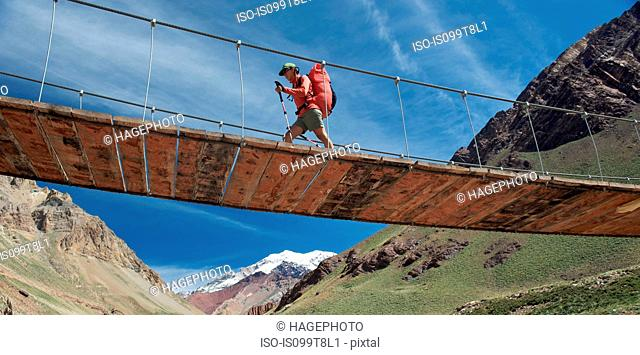 Woman crosses bridge over the Horcones River, Aconcagua in the Andes Mountains, Mendoza Province, Argentina