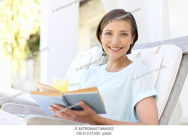 Smiling woman reading book in lawn chair
