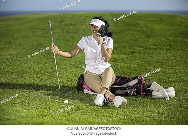 Cheerful stylish woman relaxing on golf course sitting on bag and speaking on phone happily