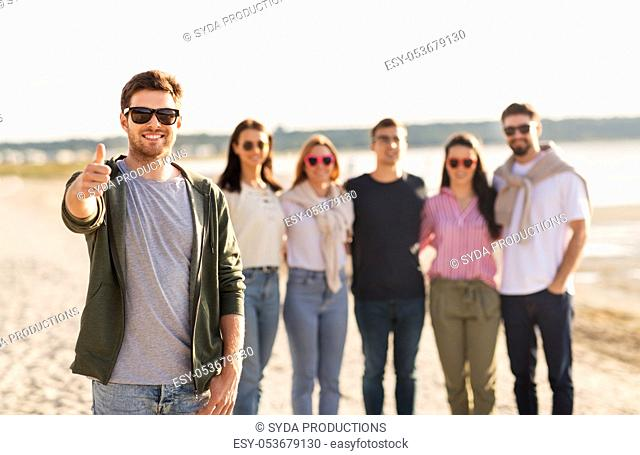 happy man with friends on beach showing thumbs up