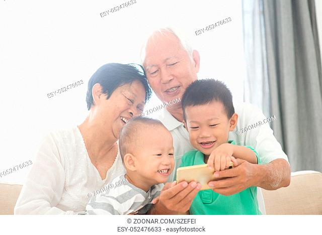 Portrait of happy Asian grandparents and grandchildren selfie using smart phone at home, family indoor lifestyle