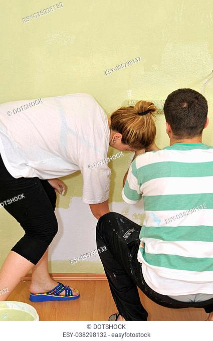 Home improvement: Young couple painting wall with paint roller