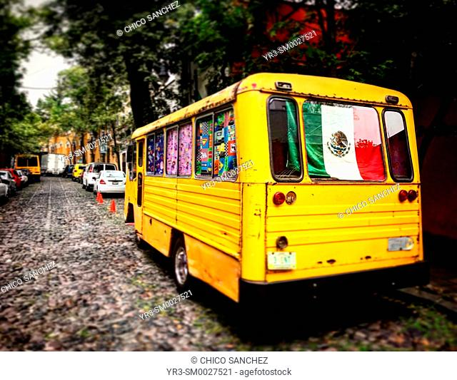 A yellow bus decorated with a Mexican Flag in San Angel, Mexico City, Mexico