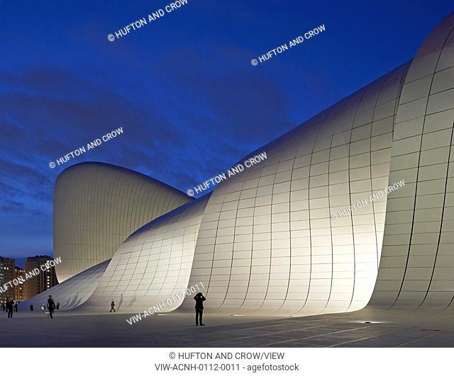 Heydar Aliyev Cultural Center, Baku, Azerbaijan. Architect: Zaha Hadid Architects, 2013. Illuminated free-form curved facade against dusk sky