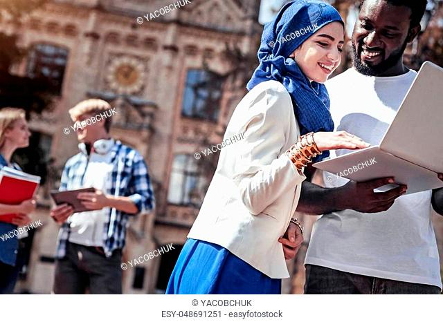 Digital natives. Happy positive young woman standing near her fellow student and using the touchpad while looking at the laptop screen
