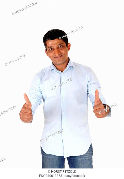 A closeup image on an East Indian man in jeans and blue shirt standing.with booths of his thumps up, isolated for white background