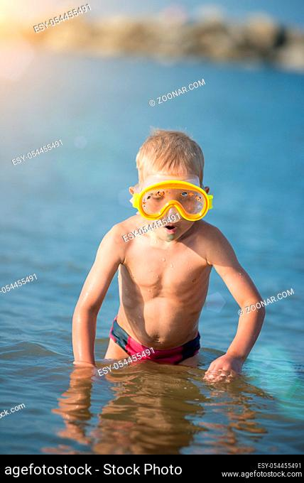 Little boy with snorkel by the sea. Cute little kid wearing mask and flippers for diving at sand tropical beach. Ocean coast