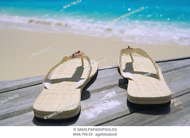 Pair of slippers on deck on beach