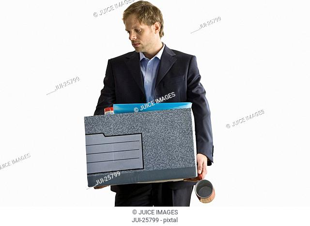 Fired businessman carrying box of personal effects