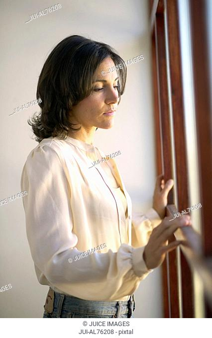 View of woman looking out the window and holding windowsill