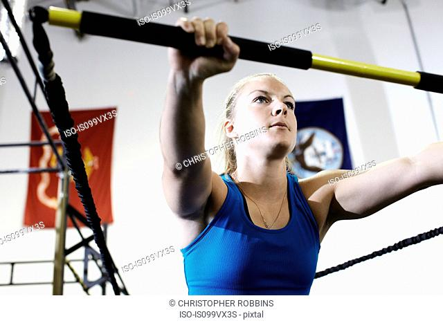 Woman working out in gym with exercise bar and resistance cord