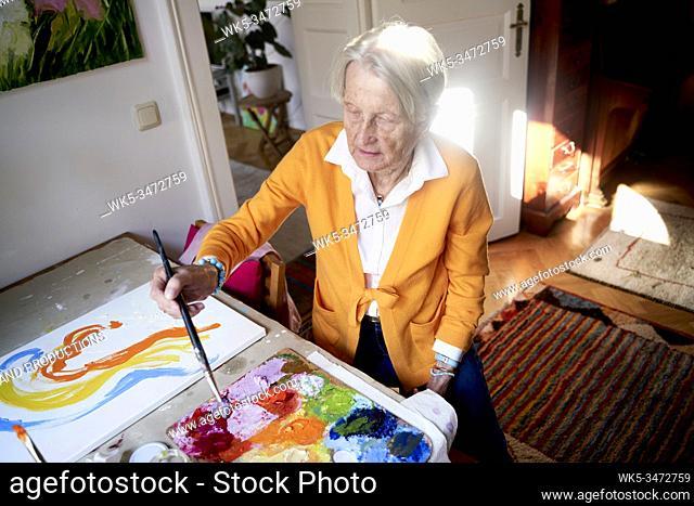 Senior woman painting at home