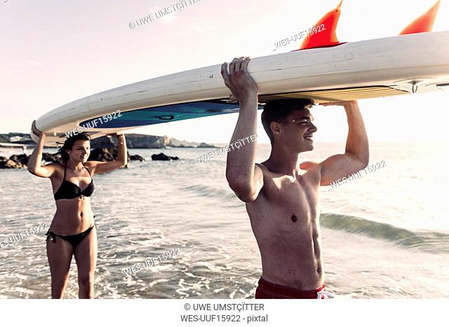 France, Brittany, happy young couple carrying an SUP board at the sea together